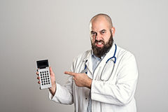 Young doctor pointing to pocket calculator royalty free stock photography
