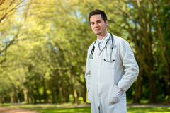 Young doctor portrait with stethoscope. On the green park background Stock Images