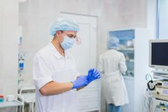Young doctor during preparation for operation. Assistant of surgeon wearing surgical mask in operation room at the. Hospital Stock Photography