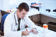 Young doctor prescribing recipe. In his ordination Royalty Free Stock Photo