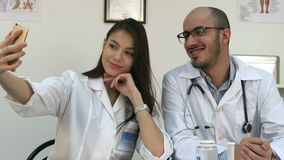 Young doctor and pretty nurse taking selfies on the phone at their workdesk stock footage