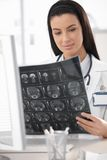 Young doctor with X-ray scan. Young doctor looking at X-ray scan in office, smiling Royalty Free Stock Photography