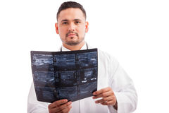 Young doctor reading x-rays. Portrait of a young x-ray technician reading some results at work on a white background Royalty Free Stock Photo