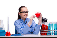 The young doctor with red heart isolated on white Stock Photos