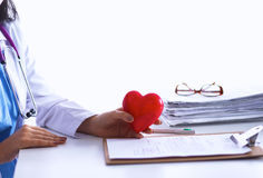Young doctor with red heart symbol sitting at desk Stock Images