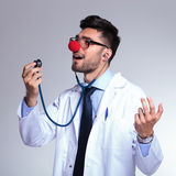 Young doctor with red nose singing in the stethoscope Royalty Free Stock Images