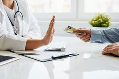 Young doctor refuses a bribe from her patient stock photography