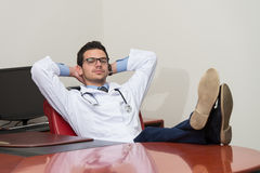 Young Doctor Relaxes Sitting In The Office Royalty Free Stock Images