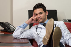 Young Doctor Relaxes Sitting In The Office Royalty Free Stock Photography
