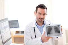 Young doctor showing radiography on a tablet Stock Images