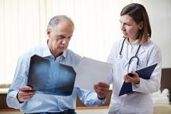 Recommendations of radiologist. Young doctor showing x-ray image to sick retired patient and giving him recommendations about medical treatment royalty free stock images