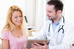 Young doctor showing results on tablet to patient Stock Photo