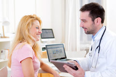 Young doctor showing results on tablet to patient Stock Image