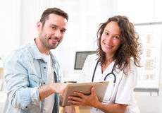 Young doctor showing results on tablet to patient Royalty Free Stock Photos