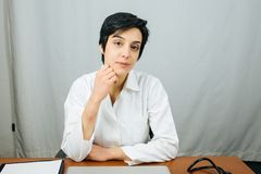 Young doctor sitting at the desk in the her office. stock photography