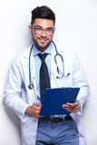 Young doctor smiles with clipboard in hand Stock Photos