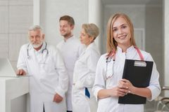 Young doctor smiling, medical staff posing behind. royalty free stock photography