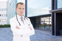 Young doctor standing on street against hospital building Stock Image