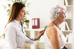 Young doctor with stethoscope exam senior woman Royalty Free Stock Photography