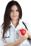 Young doctor with stethoscope gently holds a heart. Young femal doctor with stethoscope gently holds a heart Royalty Free Stock Photo