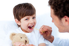 Young doctor taking little boy's temperature Royalty Free Stock Photo