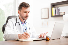 Young doctor taking notes and using a laptop Royalty Free Stock Photo