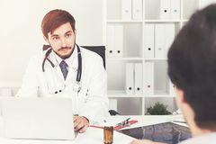 Young doctor talking to a patient in office, toned Royalty Free Stock Photo