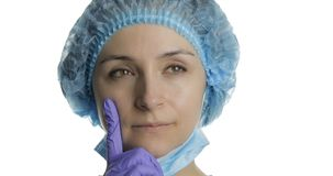 Young doctor is thinking. Adult female medical worker searching a right solution stock photography