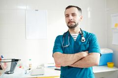 Veterinarian in clinics. Young doctor in uniform crossing his arms on chest while looking at you in his office Stock Images