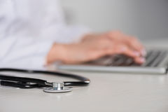 Young doctor using laptop, stethoscope lying on table on foreground Royalty Free Stock Image