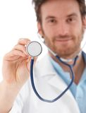 Young doctor using stethoscope smiling Royalty Free Stock Photos
