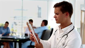 Young doctor using tablet computer. With colleagues working on the background stock footage