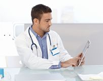 Young doctor using tablet computer. Young male doctor using tablet computer, sitting at desk in doctor's room Stock Images