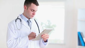 Young doctor using a tablet computer. In a office stock video