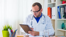 Young doctor using tablet in his  surgery. Royalty Free Stock Image