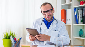 Young doctor using tablet in his  surgery. Royalty Free Stock Photos