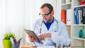 Young doctor using tablet in his  surgery. Stock Photo