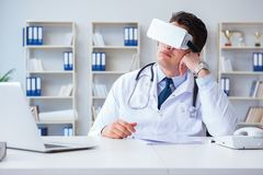 Young doctor with vr virtual reality headset working in the offi Royalty Free Stock Image