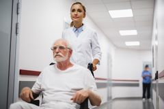 Young doctor walking with disabled old man in hospital hallway stock photo