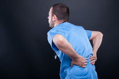 Young doctor wearing scrubs having back problem. Young doctor wearing scrubs having back or spine problem on black background with copy text space stock images