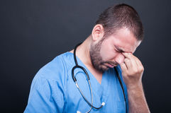 Young doctor wearing scrubs having head ache Stock Image