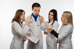Young doctor on white background. The man-a doctor and three female doctors have fun discussing the test results, white background Royalty Free Stock Photo