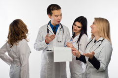 Young doctor on white background. The man-a doctor and three female doctors have fun discussing the test results, white background Stock Photos