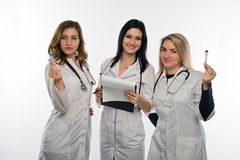 Young doctor on white background. Three female doctors looking at the test results. On a white background Stock Images