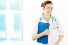 Young doctor in white and green coat with tablet Royalty Free Stock Image