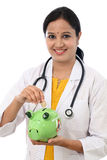 Young doctor woman holding a piggy bank Royalty Free Stock Images