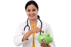 Young doctor woman holding a piggy bank Stock Photos