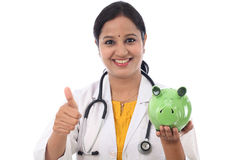 Young doctor woman holding a piggy bank Stock Image