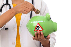 Young doctor woman holding a piggy bank. And rupe coin Stock Images