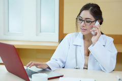 Young doctor woman speaking by phone mobile in her office Stock Photo